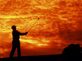 Man Swinging Golf Club at Sunset