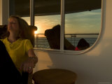 Woman Sitting on the Deck of Cruise Ship with Reflection of Sunset