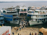 Half a Dozen Riverboats Form a Geometric Wedge as They are Being Loaded with Goods