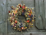 A Delicate Dried Flower Wreath Adorns a Wooden Wall Near a Window
