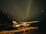 The Aurora Borealis Glows Brightly over a Seaplane Docked on Cli Lake