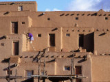 A Woman Climbs a Ladder to an Apartment in an Adobe Complex