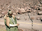 An Injured Pakistani Man Walks on an Earthquake-Damaged Mountain Pass Road