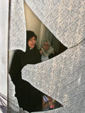 A Family are Seen Through the Shattered Window of Their House