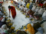 A Crowd of Women Who Pray in a Nearby Temple Six Hours a Day in Exchange for Meals and Money