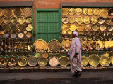 Man Walking Past Brass Platters and Trays, Luxor, Egypt