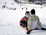 Two People on Sled at Top of Run with People Below