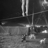 Two Small Children Watching Circus Performer Practicing on Tightrope, Her Legs Only Visible