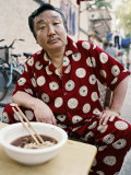 Man in Silk Pajamas Eats a Bowl of Noodles on the Street