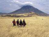 Maasai Warriors Stride across Golden Grass Plains at Foot of Ol Doinyo Lengai,