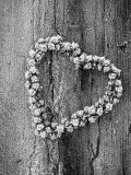 Frosted Heart-Shaped Metal Bell Wreath on Rustic Wooden Background