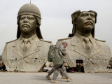 US Soldiers Stroll Past Bronze Busts of Former Iraqi President Saddam Hussein in Baghdad