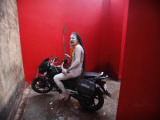 Ash Smeared Naked Hindu Holy Man, Poses on a Motorcycle at the Kumbh Mela Festival in India