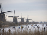 People Skate on Frozen Canals in Kinderdijk's Mill Area, a UNESCO World Heritage Site, Netherlands