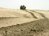 An Amphibious Assault Vehicle Rolls Through a Desert Field North of Fallujah