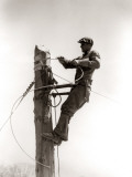 Man Worker, Working Atop Utility Pole, Installing Electric Wires For Power Utilities
