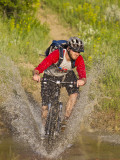 Mountain Biker Splashes Through Andrews Creek, Maah Daah Hey Trail in Medora, North Dakota, USA
