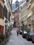 A Woman Rides a Bike Up a Cobbled Street in the Morning