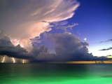 Lighting striking over green and blue water Photographic Print