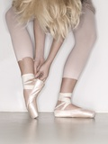 Ballerina adjusting toe shoe
