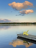 Clouds reflected in Silent Lake with Muskoka chair on dock