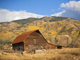 The famous Steamboat Barn, Steamboat Springs Ski Area in the background with yellow aspen trees, Co