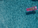A Girl Floating on a Pink Raft in a Swimming Pool