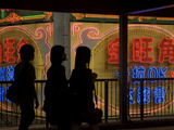 Women Walk Past Neon Signs in the Mong Kok District