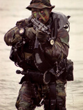 A Navy SEAL Exits the Water Armed And Alert For Action