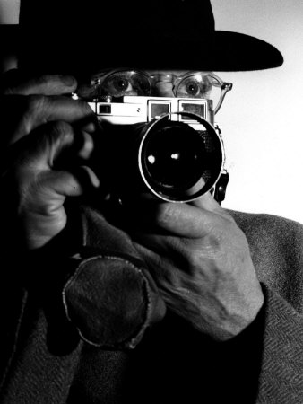 Photographer Henri Cartier-Bresson Wearing Hat And Holding Camera Up To His Face