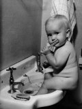 Adorable Baby Brushing Teeth While Sitting in Sink