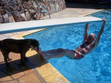 Sen Barry Goldwater Hanging Underneath Diving Board in Swimming Pool as Dog Licks His Toes