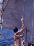 Man Raising the Sail of His Small Sailboat