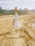 Brazilian Woman Walking Down a Sandy Road Carrying a Large Jar on Her Head