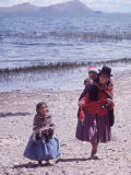 Mother and Two Children Holding Ball of Yarn  Andean Highlands of Bolivia