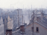 Hazy Scene of Industrial Town in East Germany Showing Rooftop Antennas and Smokestacks in Distance