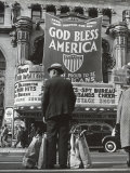 Man with Shopping Bags in Front of Million Dollar Theatre Emblazoned with God Bless America Banner