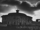 Round Stone Shaker Barn Dramatically Highlighted with Darkening Clouds