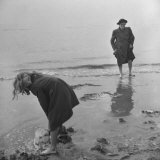Girl Playing in the Sand while an Older Woman Gets Her Feet Wet in the Ocean at Blackpool Beach