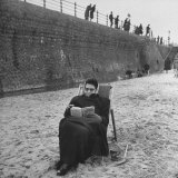 Woman Wrapped up Tightly  Reading a Book on the Beach