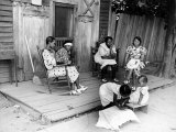 African American Women Sitting on the Porch of their Ramshackle House Watching their Children Play