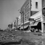 Mud and Wreckage are Piled in Front of Stores Along Desolate Main Street on North Topeka