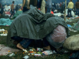 Several Youths Huddled under a Green Tarp  During the Woodstock Music and Art Fair