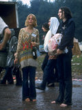 Couple Standing Barefoot on a Road Holding a Bundle and Wine Bottle  Woodstock Music and Art Fair