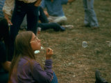 Jackie Barg Sitting on the Ground and Blowing Bubbles  During the Woodstock Music and Art Fair