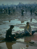Chuck Morgan Sitting in the Mud and Water with a Friend  During Woodstock Music and Art Fair