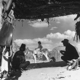 American Indians Sitting under Shelter Watching Child on Donkey