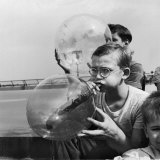 Two Young Boys Blowing Large Transparent Bubbles with a Blow-Straw Dipped in a Soft Plastic
