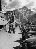 Pedestrians Walking Along Main Street in Resort Town with Cascade Mountain in the Background