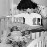 Sen John Kennedy's Wife Jacqueline Offering Baby Caroline a Silver Rattle at their Georgetown Home